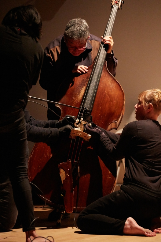 Boy climbs up double bass